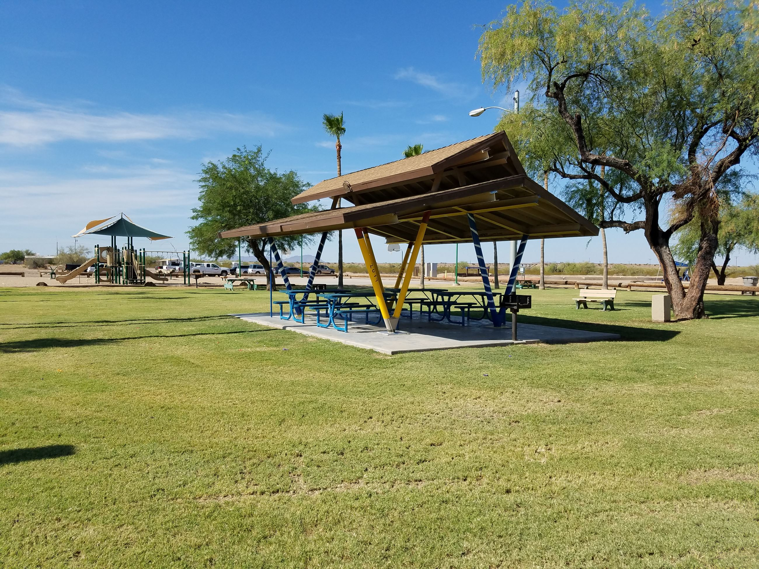 Ramada with playground in distance and grassy field at Gila Bend Rotary Park